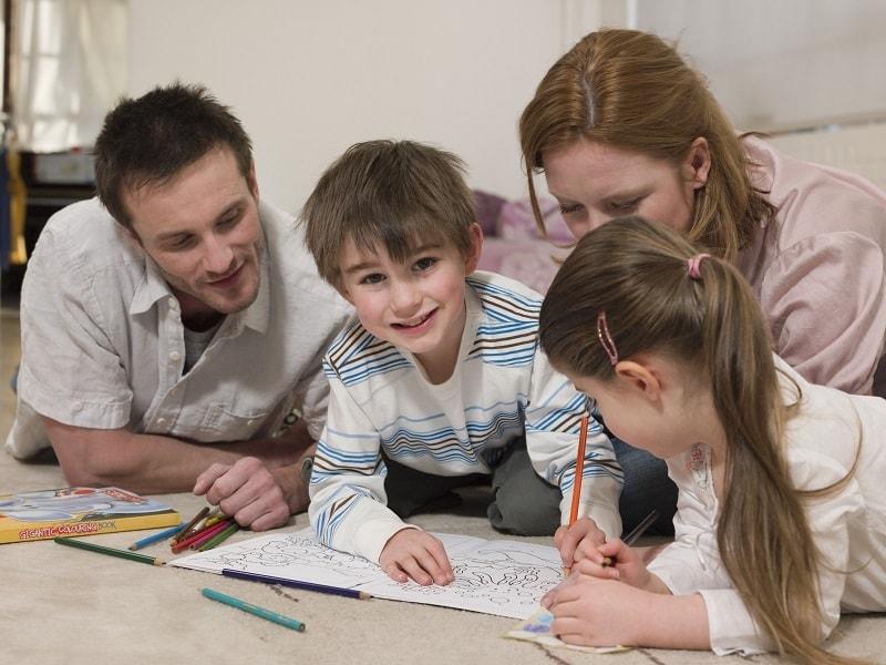 Dzieci bawią się z rodzicami, wypełniają kreatywne kolorowanki dla dzieci.